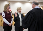 Linda Harvell takes the oath of office from Judge Ed Spillane as her daughter, Cecilee, watches.