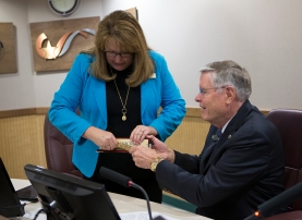 Outgoing Councilwoman Julie Schultz clears the way for newly elected Councilman John Nichols.
