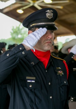 A solemn officer salutes during the 30th Annual Law Enforcement Memorial Service in May at the American Pavilion at Veterans Park and Athletic Complex.