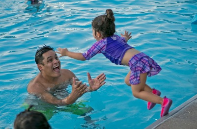 "An excited young girl jumps into the arms of her dad as they prepare to watch ""Moana"" on a 32-foot high inflatable screen at Splash-In Cinema Night at Adamson Lagoon."