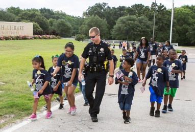 A CSPD officer walks with a group of kids in honor of Juneteenth during the annual Freedom Walk from the Lincoln Recreation Center to the Bush Library and Museum.