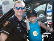 A young music fan takes a break with one of CSPDs finest during the U.S. Navy band Cruisers concert at Veterans park and Athletic Complex.