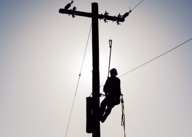 A lineman is silhouetted against the fall sky during the annual Apprentice Lineman Rodeo at Veterans Park and Athletic Complex.