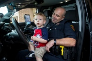 An amused College Station police officer showed his patrol car off to a young resident during the annual National Night Out in October.