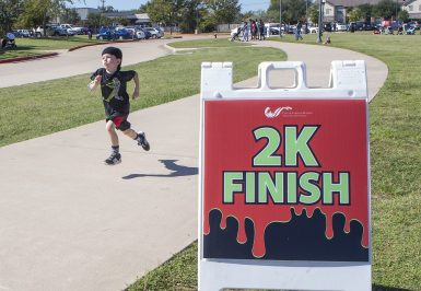 A young participant sprints across the finish line in the Todder 2K at Wolf Pen Creek Park in October.
