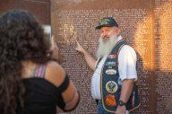 A veteran points at his name on the Wall of Honor at Veterans Park & Athletic Complex as his family captures the moment.