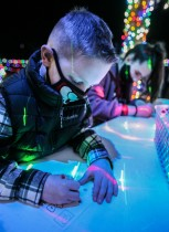 A young boy enjoys coloring while on a visit to the Christmas at Brazos Valley Tree Farm.