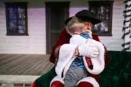 Santa hugs a small child after he hears his Christmas wish during the Jingle on The Green event at Century Square in December.
